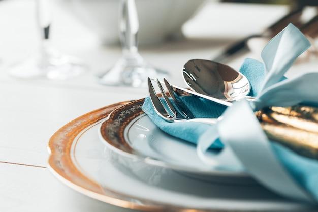 Gros plan du réglage de la table pour un dîner raffiné avec des couverts et de la verrerie