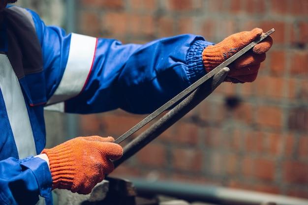 Gros plan du réparateur en constructeur professionnel uniforme travaillant à l'aide d'équipement de construction