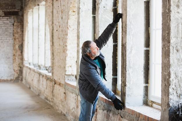 Gros plan du réparateur en uniforme, constructeur professionnel travaillant à l'aide d'équipement de construction. processus de construction, rénovation d'appartement, réparation, construction. coloration, mesure, préparation de la base.