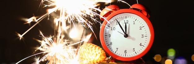 Gros plan du réveil rouge montrant cinq avant minuit