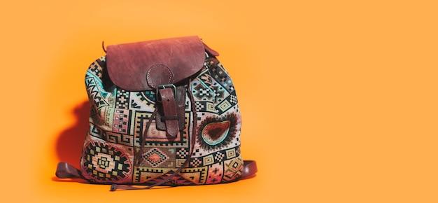 Gros plan du sac à dos de voyage vintage sur orange
