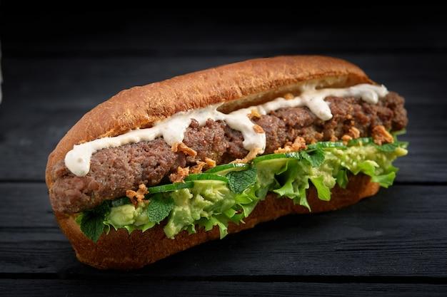 Gros plan du sandwich kebab sur fond de bois noir
