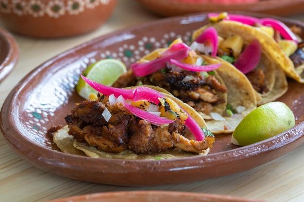 Gros plan du savoureux tacos de pastor mexicain dans une assiette