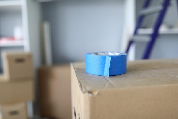 Gros plan du scotch bleu portant sur le dessus du carton