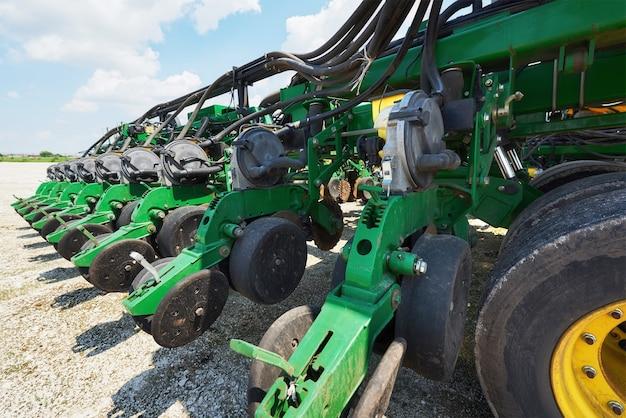 Gros plan du semoir attaché au tracteur dans le champ.