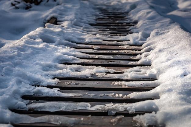 Gros plan du sentier en bois couvert de neige le sentier est pavé de planches de bois