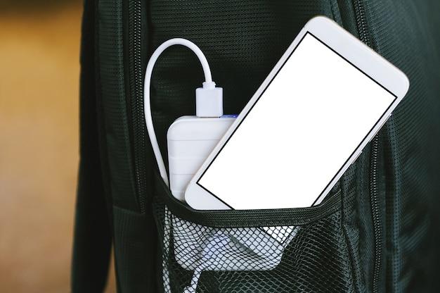 Gros plan du smartphone et de la banque d'alimentation dans le sac à dos