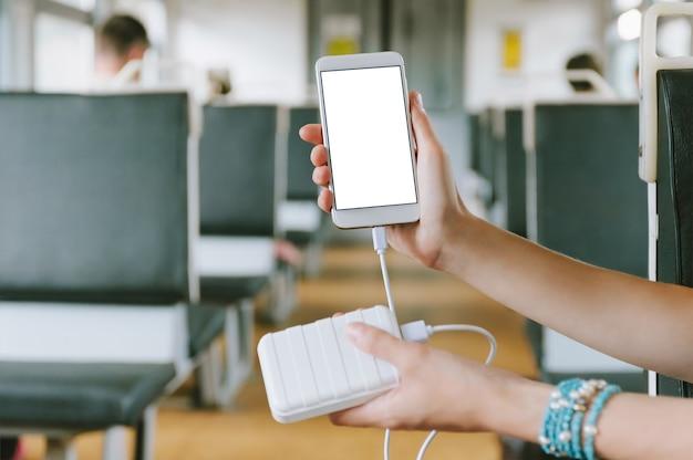 Gros plan du smartphone et de la banque d'alimentation en main
