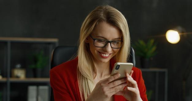 Gros plan du smartphone dans les mains de la femme d'affaires blonde. heureux message texte féminin et en tapant sur le téléphone portable dans l'armoire.