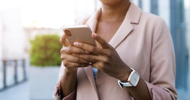Gros plan du smartphone entre les mains de la jeune femme d'affaires afro-américaine tout en appuyant sur et en faisant défiler l'écran. femme sms sur téléphone mobile en plein air. femme à l'aide de gadget.