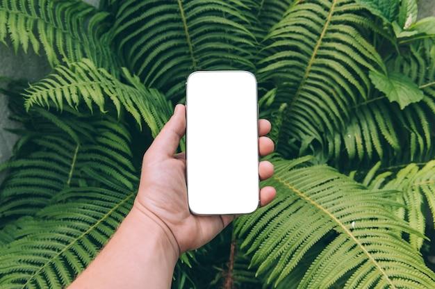 Gros plan du smartphone en main contre la verdure