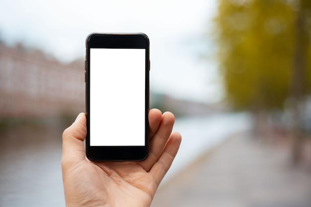 Gros plan du smartphone avec maquette en main de jeune fille.