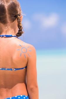 Gros plan du soleil peint par la crème solaire sur l'épaule de l'enfant