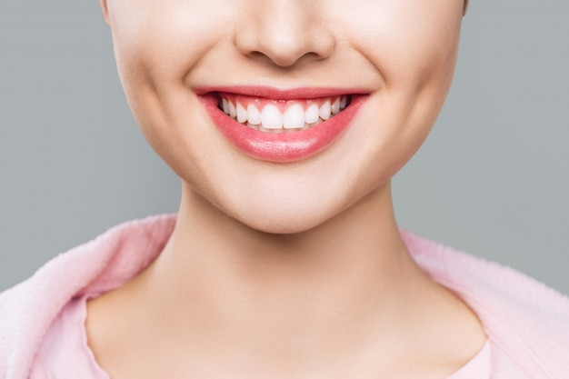 Gros plan du sourire avec des dents saines blanches.