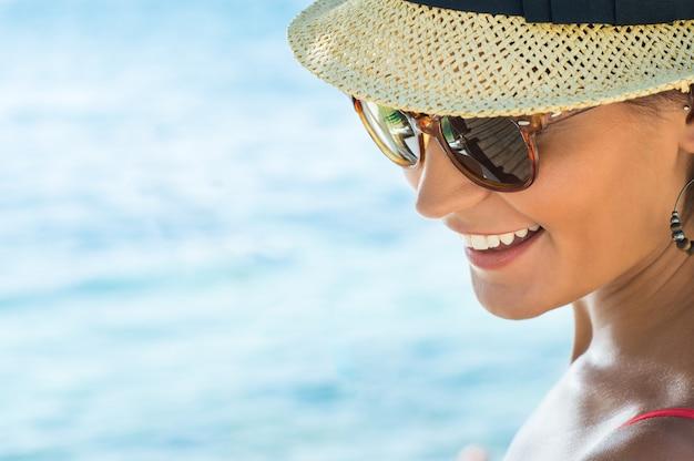 Gros plan du sourire de jeune femme portant des lunettes de soleil