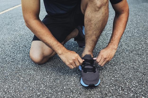 Gros plan du sportif attachant des chaussures de course