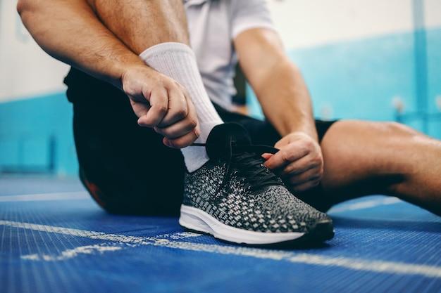 Gros plan du sportif attachant les lacets alors qu'il était assis dans la salle de sport.