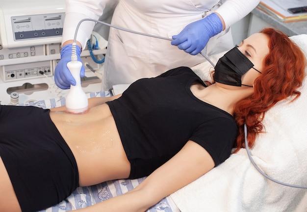 Gros plan du stimulateur électrique sur le ventre de la femme.