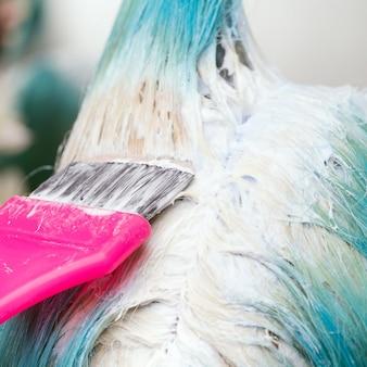 Gros plan du styliste à l'aide d'un pinceau rose tout en appliquant de la peinture à une cliente avec une couleur de cheveux émeraude