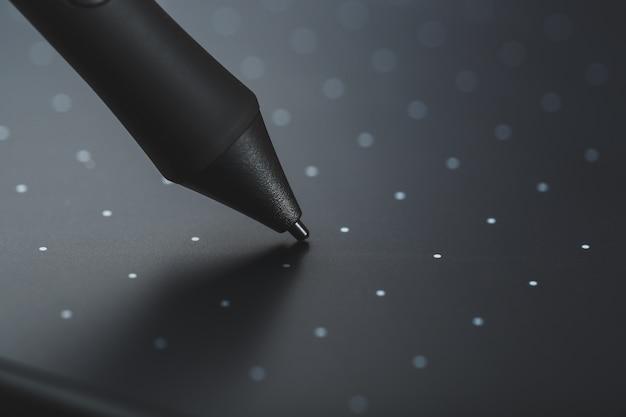 Gros plan du stylo et de la tablette graphique sur un fond texturé gris. gadget pour travailler en tant que designer, artiste et photographe.