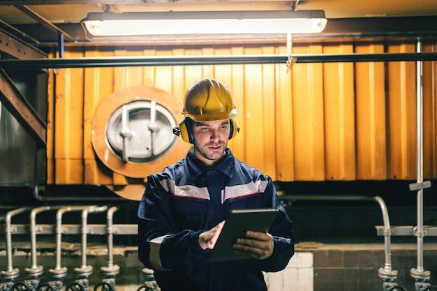 Gros plan du superviseur vêtu d'une combinaison de protection à l'aide d'une tablette en se tenant debout dans une centrale thermique.