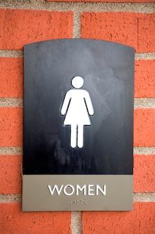 Gros plan du symbole de la femme, texte et braille sur un panneau de toilettes publiques