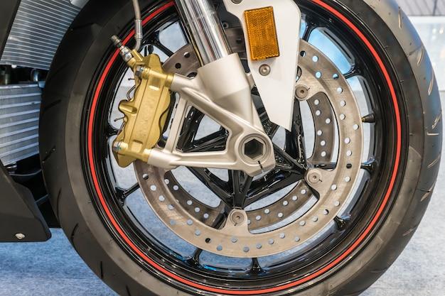 Gros plan du système de suspension et de frein à disque de la roue avant de la moto moderne. sélectionnez le focus.