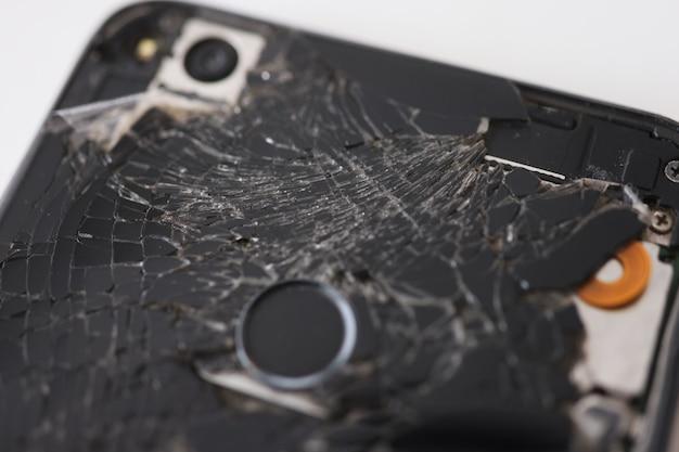 Gros plan du téléphone portable cassé noir dans l'atelier de réparation et d'entretien du concept de téléphones portables