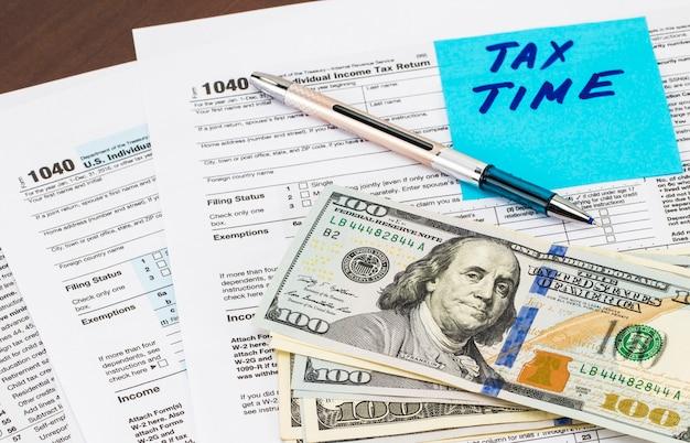 Gros plan du temps des impôts - écrit sur un pense-bête avec de l'argent.