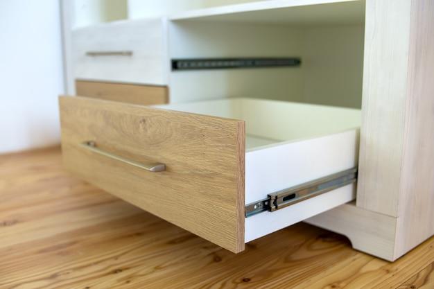 Gros plan du tiroir en bois dans une armoire contemporaine.