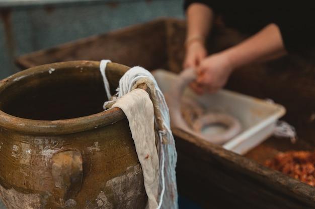 Gros plan du tissu sur un pot en argile avec une personne préparant un kielbasa sur le flou