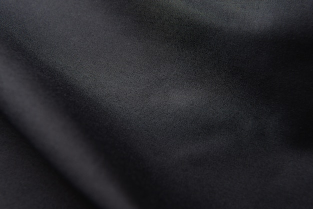 Gros plan du tissu de soie noir ondulé, fond de texture de tissu noir