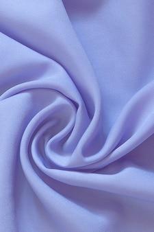 Gros plan du tissu de soie violet ondulé, beau et lisse fond de soie
