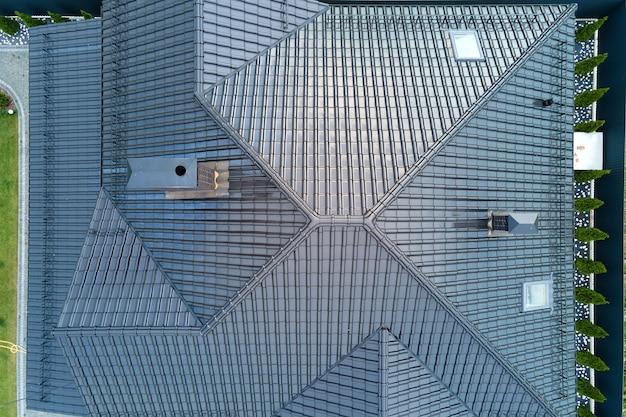 Gros plan du toit de la maison recouvert de bardeaux de céramique brillants.