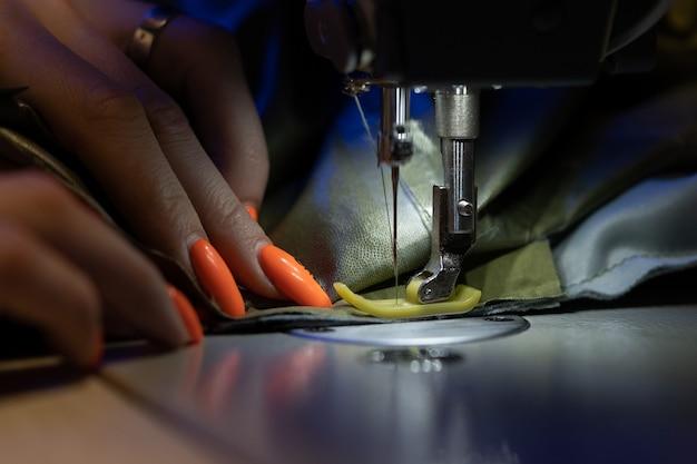 Gros plan du travail de tailleur féminin sur des modèles de tissu de point de machine à coudre pour l'industrie du vêtement