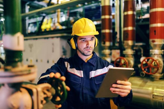 Gros plan du travailleur waring combinaison de protection lors de l'utilisation de la tablette et le serrage de la valve tout en se tenant dans l'usine de chauffage.