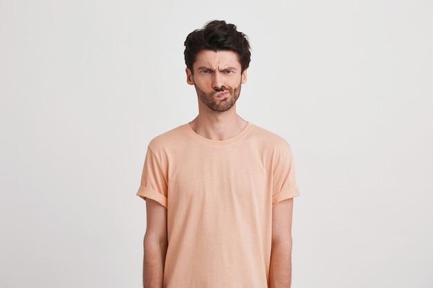Gros plan du triste jeune homme insatisfait avec des poils porte un t-shirt pêche se sent mécontent et fronçant les sourcils isolé sur blanc