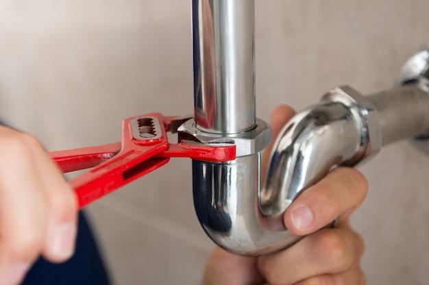 Gros plan du tuyau de fixation plombier avec clé