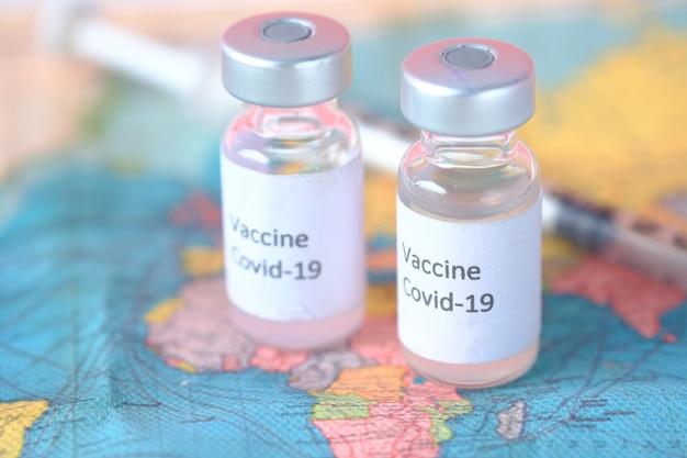 Gros plan du vaccin contre le coronavirus et de la seringue sur une carte de voyage