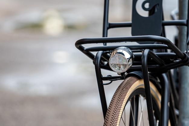 Gros plan du vélo moderne verrouillé sur une clôture métallique