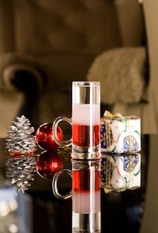 Gros plan du verre à cocktail avec de la vodka sur table avec présent et pomme de pin, scène festive.