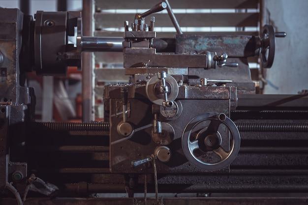 Gros plan du vieux tour métallique travaillant contre l'arrière-plan intérieur industriel de l'usine.
