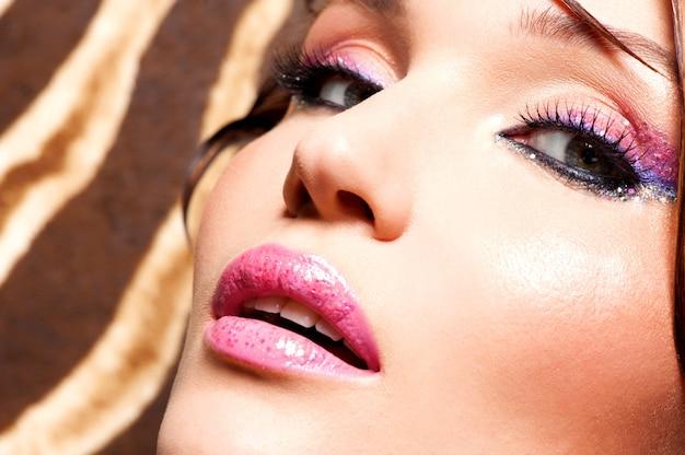 Gros plan du visage de la belle femme avec un maquillage lumineux fashion