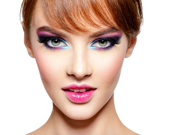 Gros plan du visage d'une belle femme avec un maquillage vif et lumineux. mannequin avec maquillage pour les yeux créatif - isolé sur blanc. fille aux cheveux roux. coiffure courte avec frange