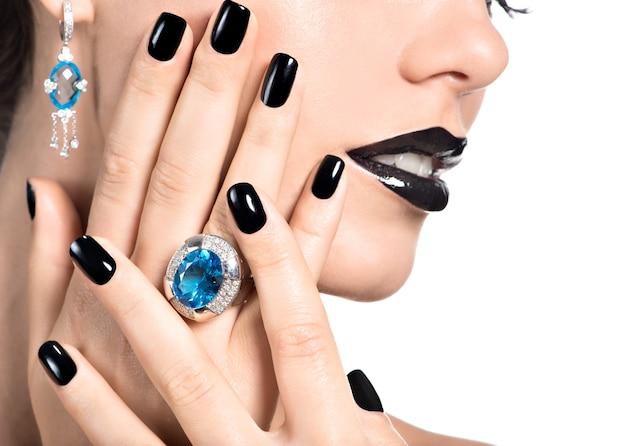 Gros plan du visage de la belle jeune femme avec manucure noire et maquillage lumineux fashion