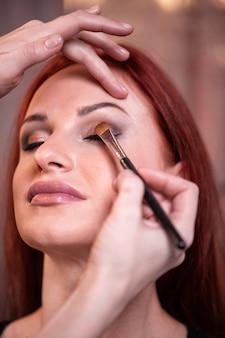 Gros plan du visage de la belle jeune femme avec le maquillage de beauté, la peau douce et fraîche et les longs cils noirs épais appliquant le mascara avec une brosse cosmétique.