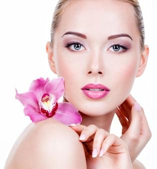 Gros plan du visage d'une belle jeune femme avec un maquillage pour les yeux violet et les lèvres. jolie fille adulte avec une fleur près du visage. - isolé sur un mur blanc