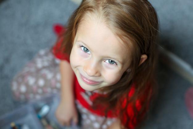 Gros plan du visage d'une belle petite fille mignonne aux yeux bleus