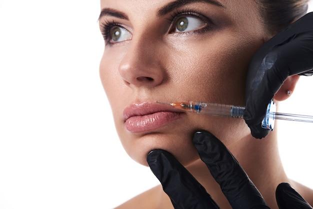 Gros plan du visage de femme attrayante isolé sur blanc et les mains des esthéticiennes dans les gants faisant injection de beauté sur les lèvres.