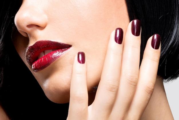 Gros plan du visage d'une femme avec de belles lèvres rouges sexy et des ongles foncés